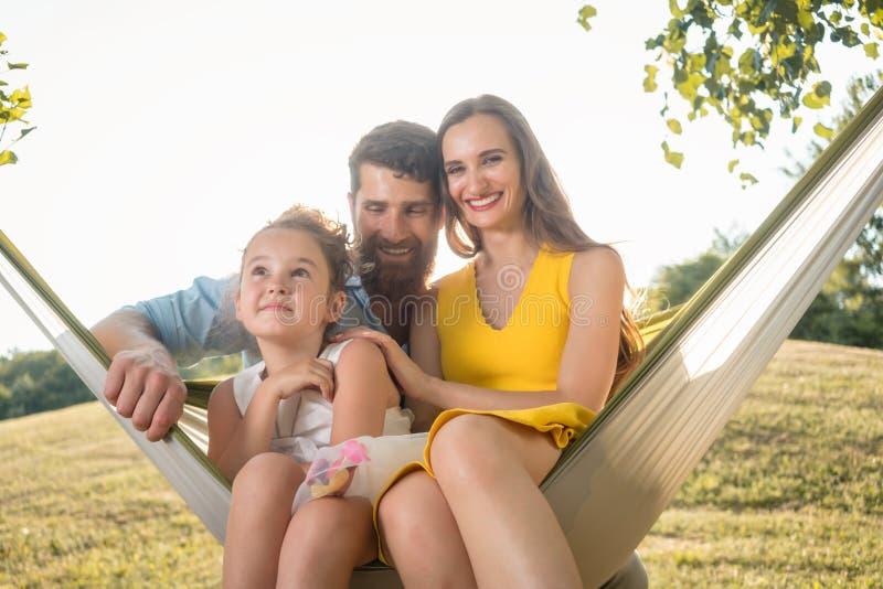 愉快的美丽的摆在与他们的女儿一起的妇女和英俊的丈夫 免版税库存照片