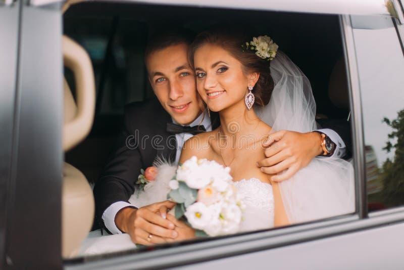 愉快的美丽的新郎和新娘有新娘花束的,发型在汽车 免版税库存图片