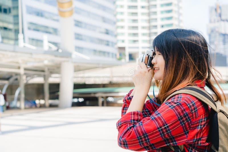 愉快的美丽的旅客亚裔妇女运载背包 使用照相机的年轻快乐的亚裔妇女对做照片在城市期间游览 库存照片