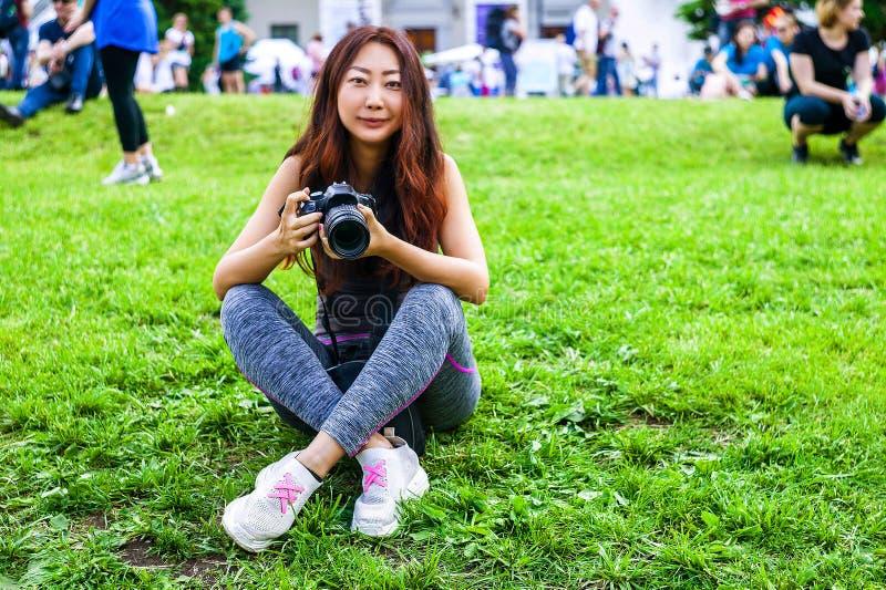 愉快的美丽的有照相机的旅客亚裔妇女 使用照相机的年轻快乐的亚裔妇女对做照片在城市游览时 免版税图库摄影