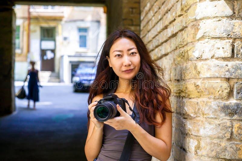 愉快的美丽的有照相机的旅客亚裔妇女 使用照相机的年轻快乐的亚裔妇女对做照片在城市游览时 免版税库存图片
