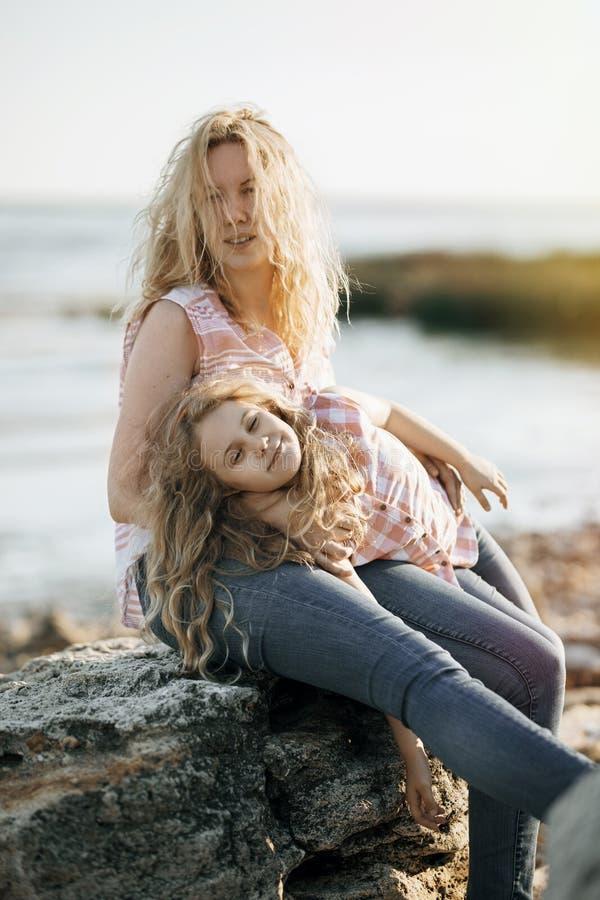 愉快的美丽的母亲和她的女儿获得在多岩石的海滩的乐趣在日落 库存图片