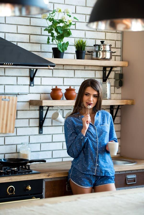 愉快的美丽的深色的妇女在有一杯茶的厨房或咖啡在蓝色睡衣 清早上升是好习性 库存照片