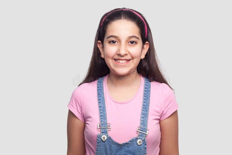 愉快的美丽的深色的少女画象便装样式、桃红色T恤杉和蓝色站立和看的牛仔布总体的 库存图片