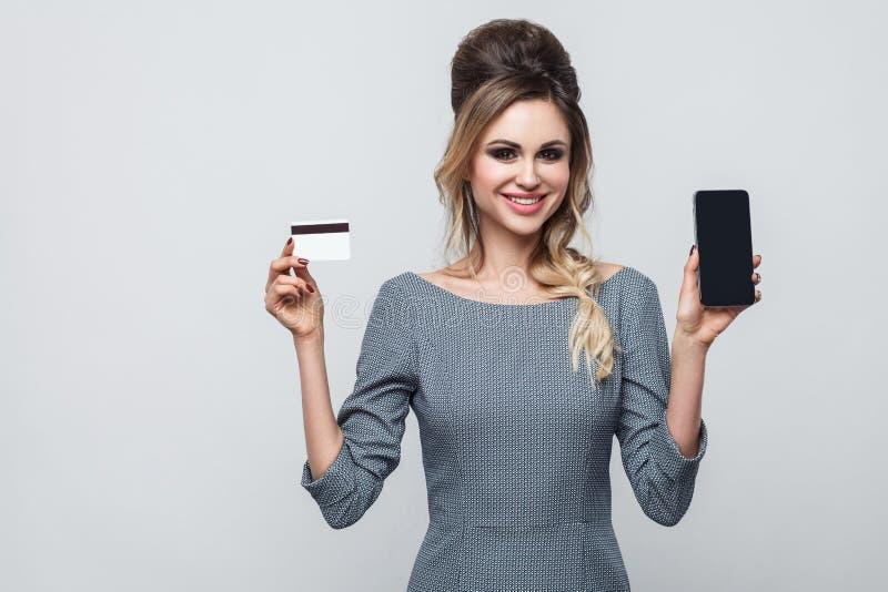 愉快的美丽的现代少女画象灰色礼服身分、固定的单元电话和信用卡的与暴牙的微笑, 库存图片