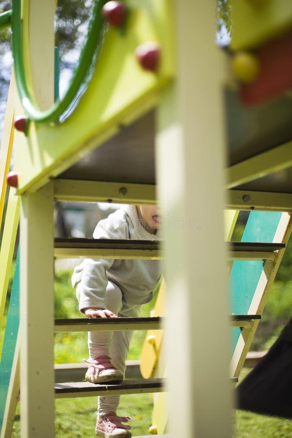 愉快的美丽的矮小的红头发人女孩攀登在操场的幻灯片 库存图片