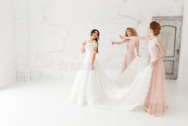 愉快的美丽的调整她的婚礼礼服的新娘和女傧相 饮用的香宾 免版税库存图片