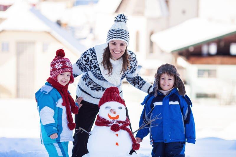 愉快的美丽的系列组装雪人在庭院,冬时里, 免版税库存图片