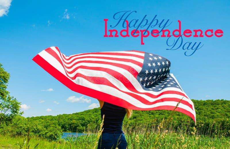愉快的美国独立日,第4 7月 拿着美国国旗的年轻女人 免版税库存图片