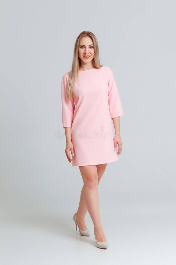 愉快的美女全长画象摆在演播室的桃红色礼服的隔绝在白色背景 免版税图库摄影
