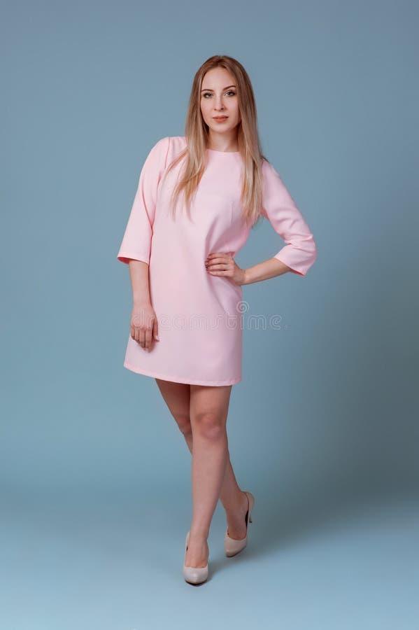 愉快的美女全长画象摆在演播室的桃红色礼服的隔绝在蓝色背景 库存照片