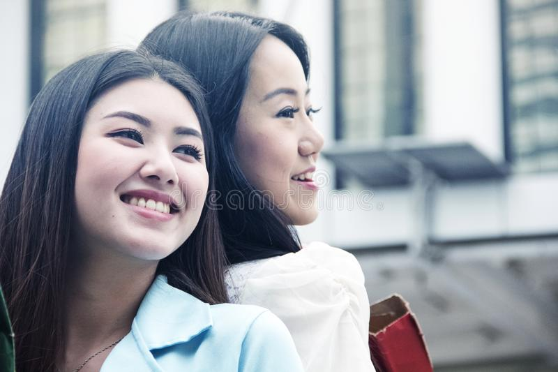 愉快的美女和走的购物在城市 免版税库存图片