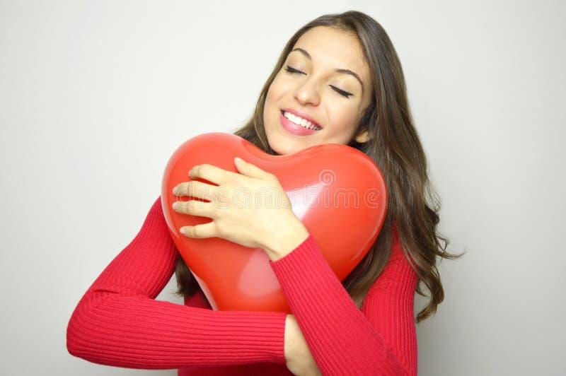 愉快的美好的在灰色背景的女孩拥抱红色心脏气球 华伦泰` s日概念 库存照片