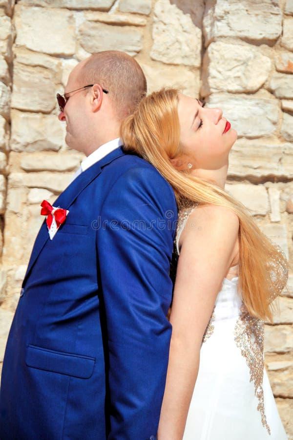 愉快的美好的婚礼夫妇,由享用太阳的墙壁 库存照片