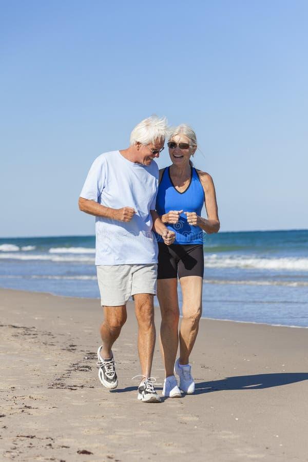 健康资深夫妇跑的跑步在海滩 免版税库存照片