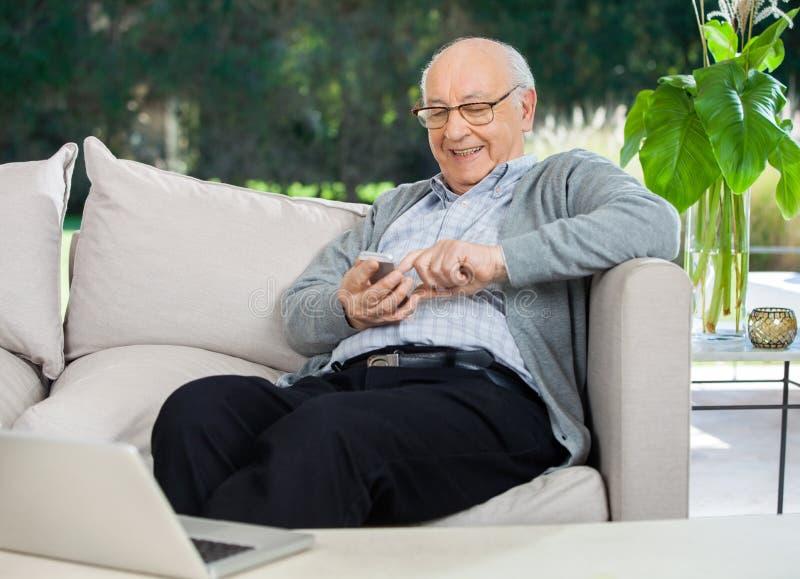 愉快的老人正文消息通过智能手机 免版税库存图片