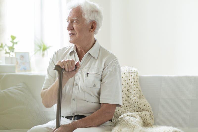 愉快的老人用放松在护理房子里的拐棍 库存图片