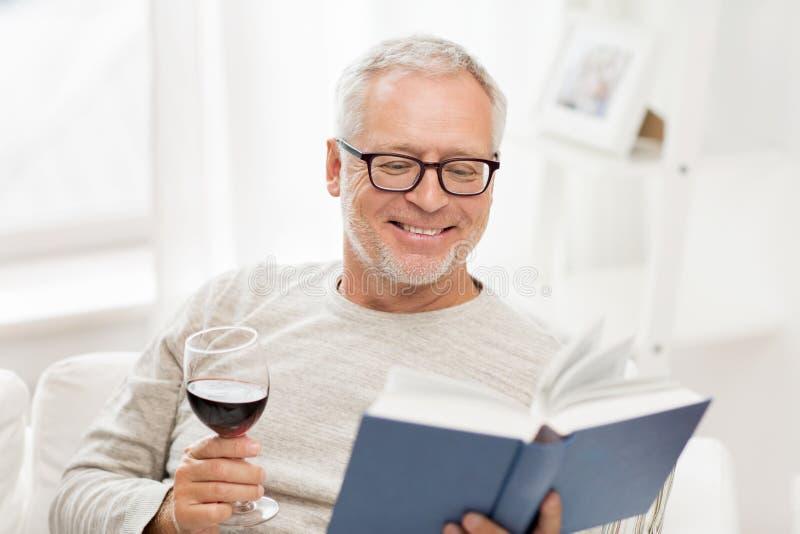 愉快的老人饮用的酒和阅读书 免版税库存图片