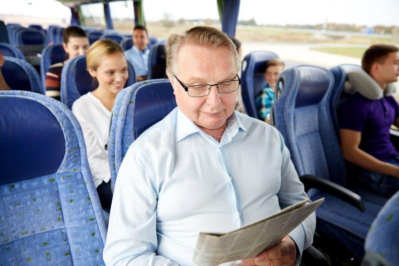 愉快的老人读书报纸在旅行公共汽车上 免版税库存照片