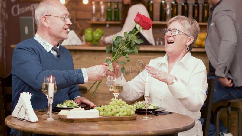 愉快的老加上玫瑰在进餐时间期间在餐馆 库存图片