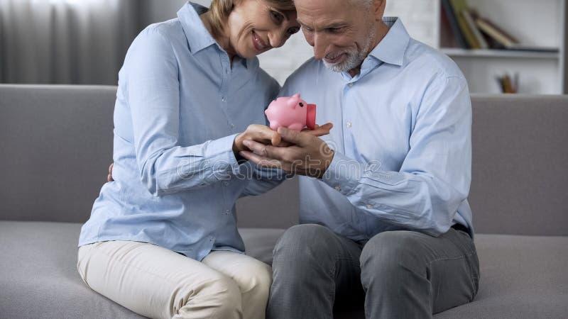 愉快的老夫妇坐有存钱罐的长沙发,可靠的金融服务 免版税库存照片