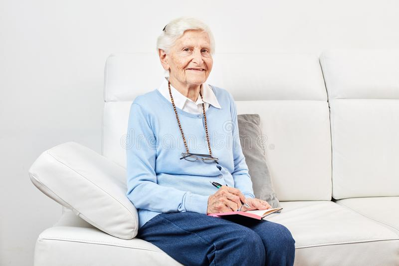 愉快的老妇人坐沙发 免版税库存照片