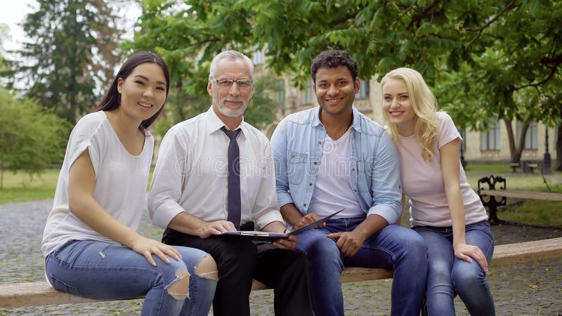 愉快的老师和不同种族的学生坐长凳,微笑入照相机 图库摄影