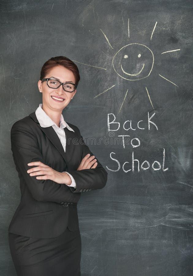 愉快的老师和微笑的太阳在黑板 图库摄影