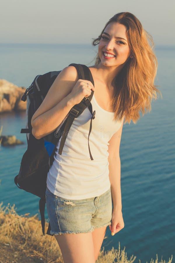 愉快的背包徒步旅行者女孩在岩石站立  库存图片