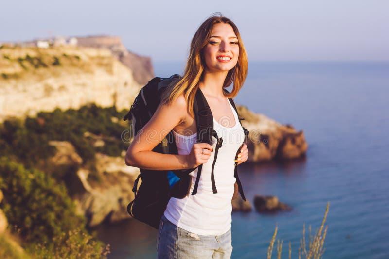 愉快的背包徒步旅行者女孩在岩石站立  免版税库存照片