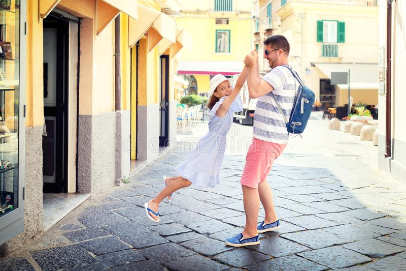 愉快的花费时间的父亲和女儿一起获得乐趣在城市街道、演奏圆环的微笑的爸爸和女孩上在rosie附近 免版税库存图片