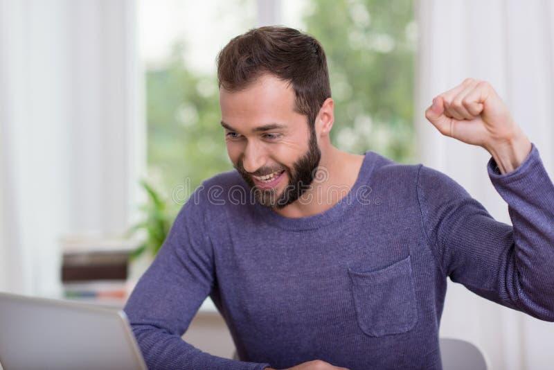 愉快的英俊的在膝上型计算机的人读的好消息 库存图片
