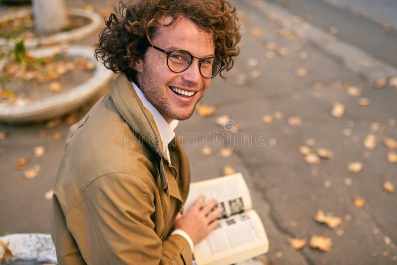 愉快的英俊的年轻人看书背面图户外 学院男生运载的书在秋天街道的校园里 免版税库存图片