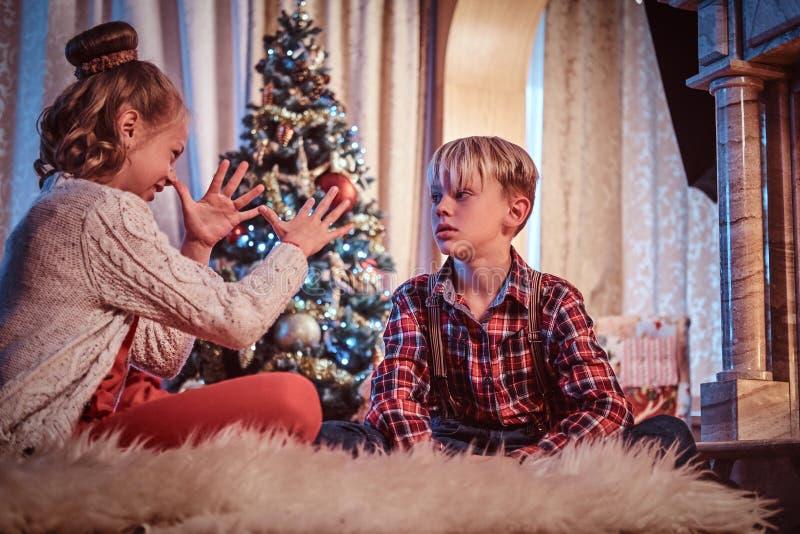 愉快的获得兄弟和的姐妹乐趣,当在家时坐毛皮地毯在圣诞树附近 免版税库存图片