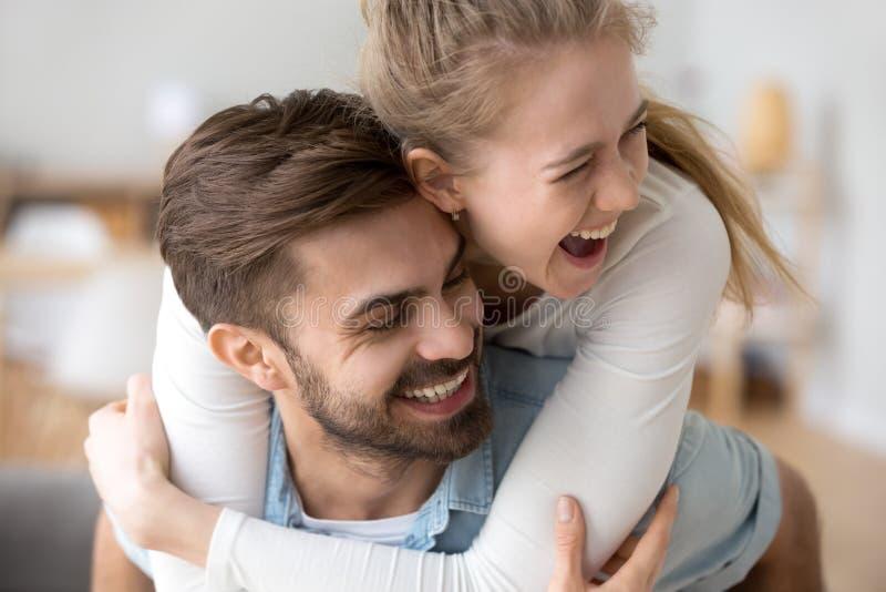 愉快的获得妇女肩扛爱的男朋友乐趣在家 免版税库存图片