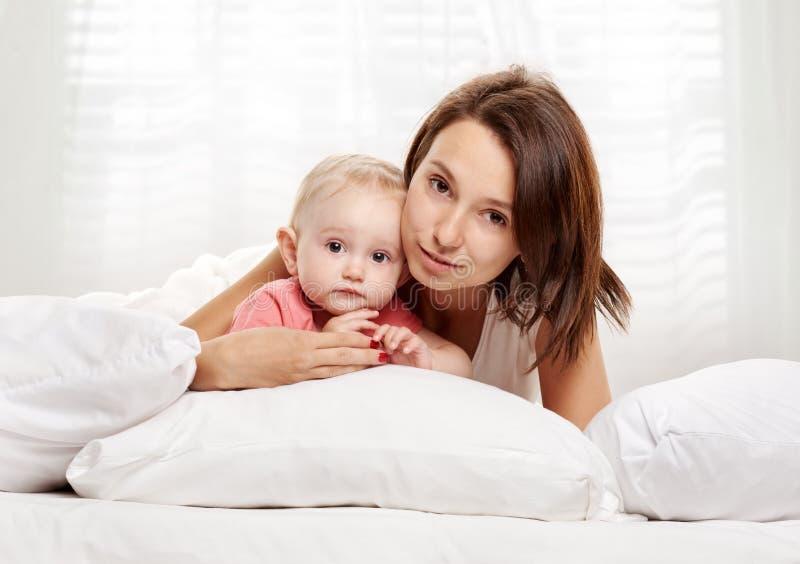愉快的获得家庭母亲和的婴孩在床上的乐趣 免版税库存照片