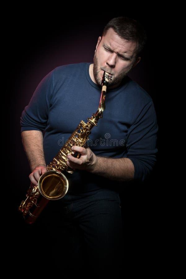 愉快的萨克斯管吹奏者演奏在萨克斯管的音乐 免版税库存照片