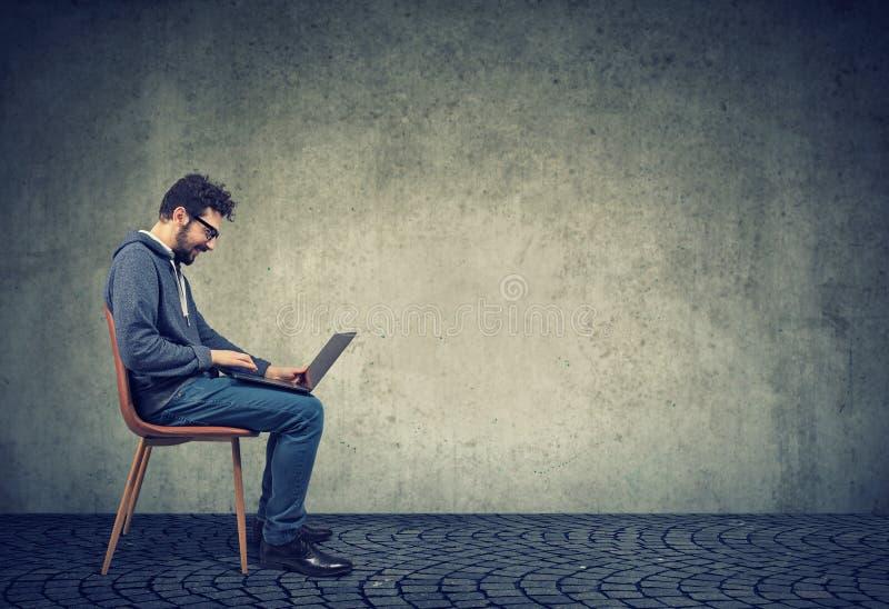 愉快的行家人坐椅子使用他的膝上型计算机 免版税库存图片