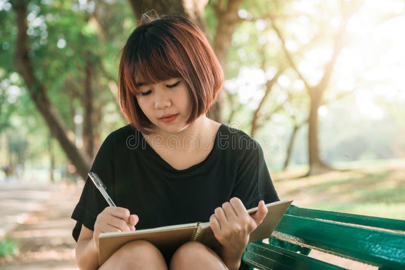 愉快的行家年轻亚洲妇女文字到她的日志里在公园 愉快的工作在笔记本的行家年轻亚裔妇女在公园 库存图片