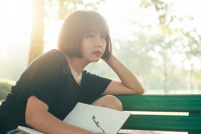 愉快的行家年轻亚洲妇女文字到她的日志里在公园 愉快的工作在笔记本的行家年轻亚裔妇女在公园 免版税图库摄影