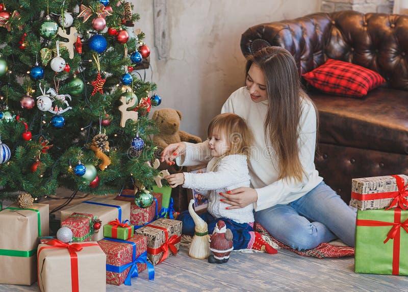 愉快的装饰圣诞树的母亲和孩子 库存照片