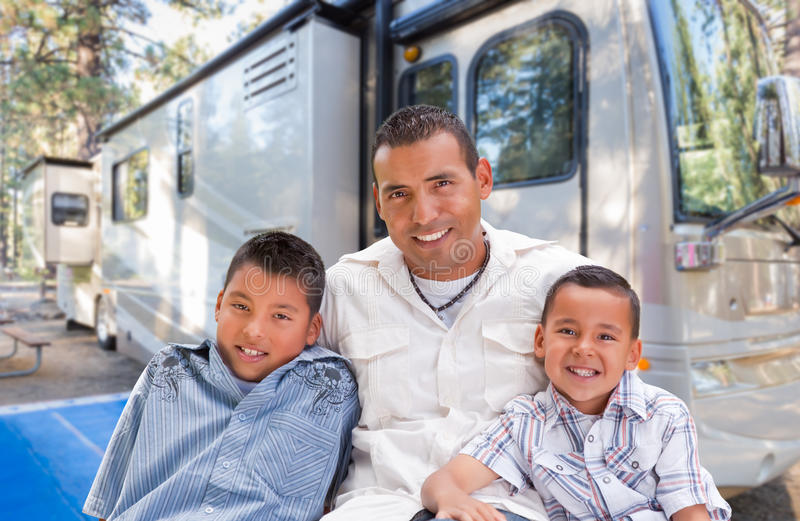 愉快的西班牙父亲和儿子在他们美丽的RV前面 库存照片