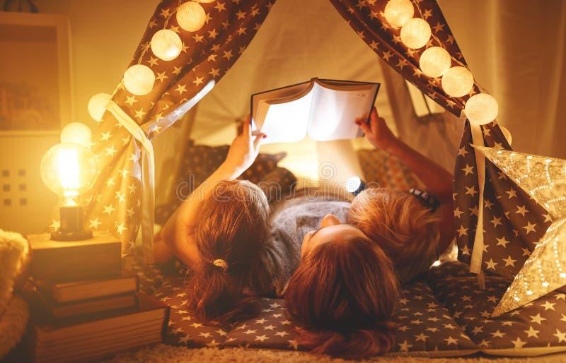 愉快的读在帐篷的家庭母亲和孩子一本书在hom 免版税库存照片