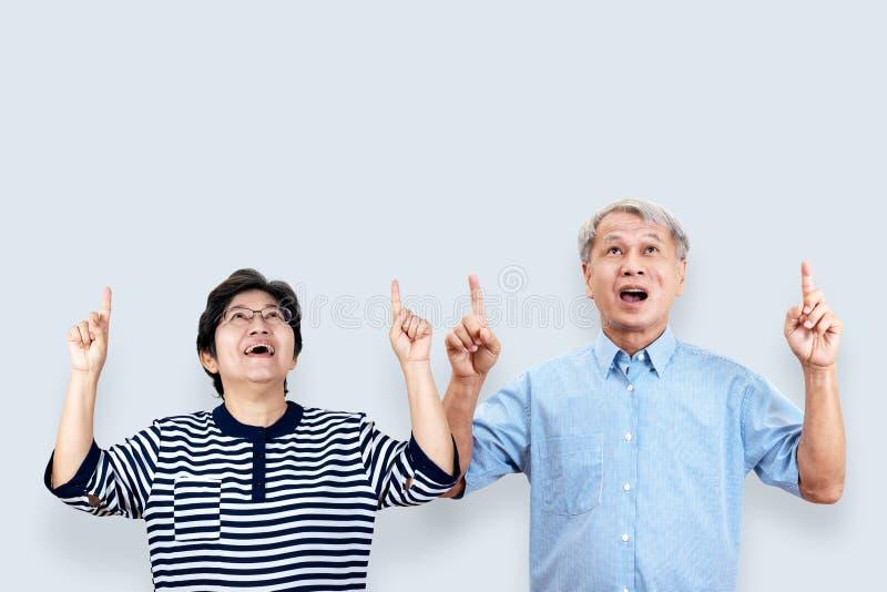愉快的资深亚洲夫妇画象打手势或指向手和手指和看上面在感觉p的背景 库存照片