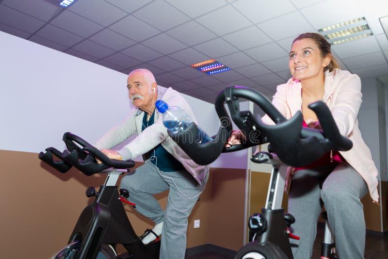 愉快的资深人民编组行使在健身房的转动的类 免版税库存图片