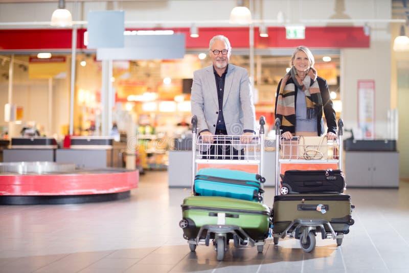 愉快的资深企业加上在推车的行李在机场 免版税库存图片