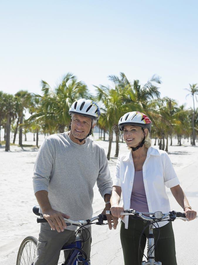 愉快的资深加上在海滩的自行车 库存图片