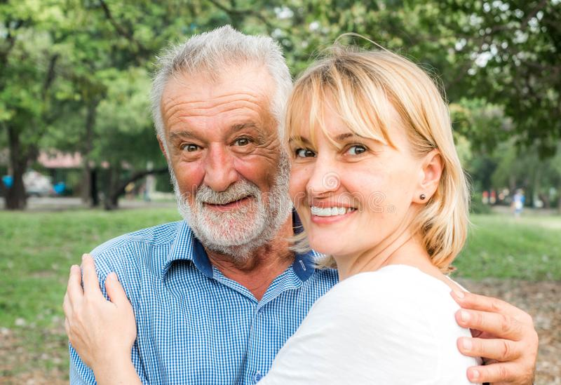 愉快的资深夫妇一起在夏天公园,一起是和停留强的,幸福生活 免版税库存照片