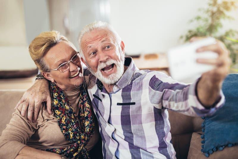 愉快的资深夫妇一起坐一个沙发在他们的客厅 图库摄影