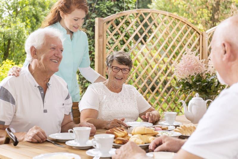 愉快的资深夫妇吃早餐的和护士照料  免版税库存照片